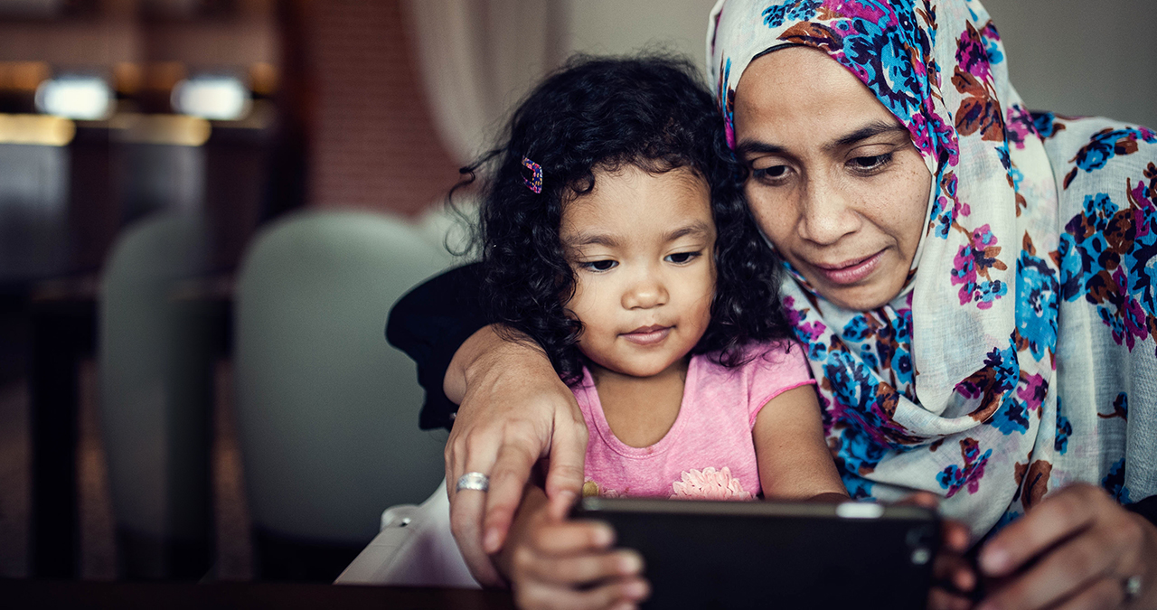 A promising future we can work towards in solving the housing affordability crisis (a mother showing her young daughter something nice and interesting on an ipad)